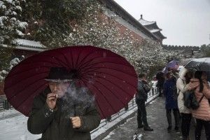 BEIJING, CHINA - NOVEMBER 22:  A Chinese man smokes as he shields himself under an umbrella from the snow during a snowfall on November 22, 2014 outside the Forbidden City in Beijing, China. China's capital and other parts of northern China had its second snowfall of the year Sunday.  (Photo by Kevin Frayer/Getty Images)