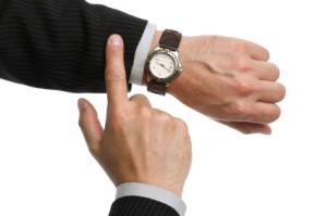 A businessman checking the time on his wrist watch