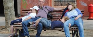 BKTM5X Whole family asleep on a park bench in Venice, Italy